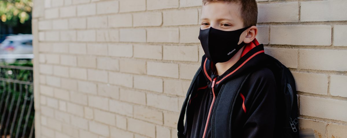 A young student leaning on a wall wearing a face mask a face and